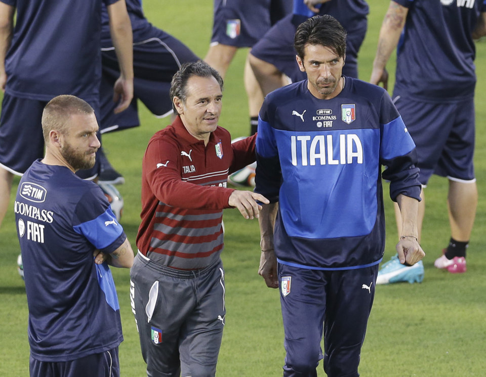 Photo - Italy head coach Cesare Prandelli, center, instructs goalkeeper Gianluigi Buffon, right, and midfielder Daniele De Rossi during a training session of the Italian national soccer team in Natal, Brazil, Saturday, June 21, 2014. Italy proved ineffective in a 1-0 loss to Costa Rica on Friday and now the Azzurri need a win or a draw against Uruguay on Tuesday to reach the second round of the World Cup. (AP Photo/Antonio Calanni)