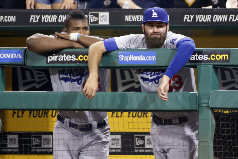 Photo - Los Angeles Dodgers' Yasiel Puig, left, and Scott Van Slyke stand in the dugout during the ninth inning of a baseball game against the Pittsburgh Pirates in Pittsburgh Tuesday, July 22, 2014. The Pirates won 12-7. (AP Photo)