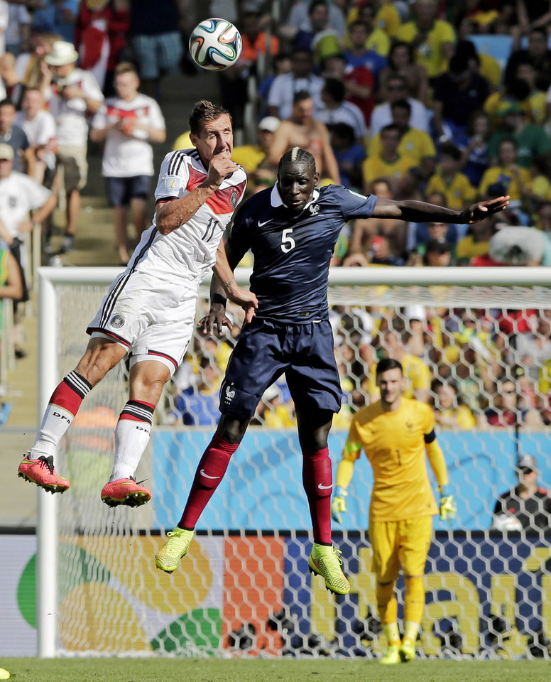 Photo - Germany's Miroslav Klose heads the ball against France's Mamadou Sakho during the World Cup quarterfinal soccer match at the Maracana Stadium in Rio de Janeiro, Brazil, Friday, July 4, 2014. (AP Photo/Matthias Schrader)