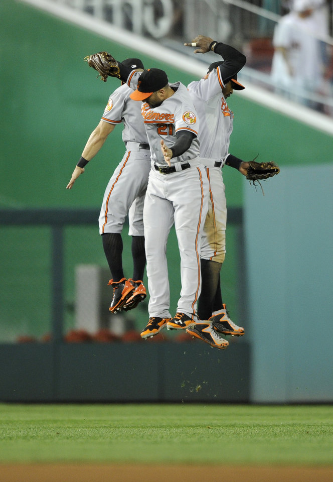 Photo - Baltimore Orioles' Nick Markakis, center, Adam Jones, right, and David Lough, left, celebrate  the 7-3 win over the Washington Nationals in a baseball game, Monday, Aug. 4, 2014, in Washington. (AP Photo/Nick Wass)