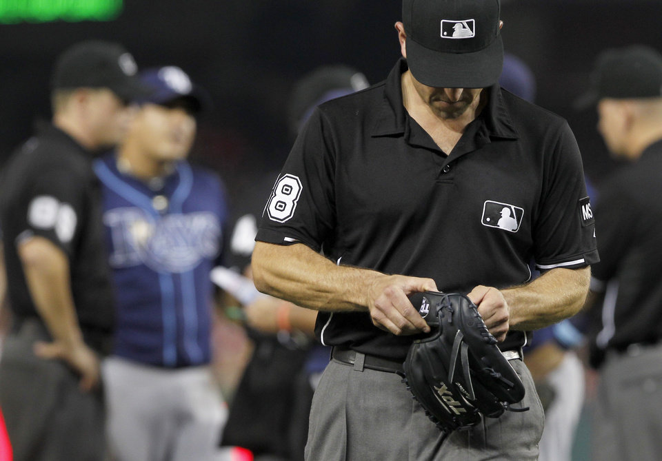 Photo - FILE - In this June 9, 2012 file photo, umpire Chris Guccione leaves with the glove of Tampa Bay Rays relief pitcher Joel Peralta after Peralta was ejected in the eighth inning for having a foreign substance on his glove during a baseball game against the Washington Nationals in Washington. Ex-minor leaguer turned law school grad Garrett Broshuis says there is cheating in baseball, all the time. (AP Photo/Alex Brandon, File)