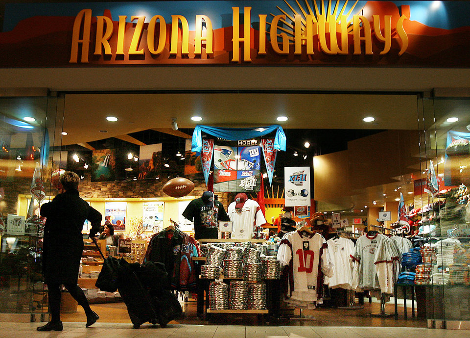 Photo - In this Jan. 29, 2008 file photo, Super Bowl merchandise is on full display in the Arizona Highways retail store at Phoenix Sky Harbor International Airport in Phoenix. Visitors spend money at NFL-funded events and buy NFL-branded memorabilia during Super Bowl week instead of frequenting local establishments, according to Philip Porter, an economics professor at the University of South Florida.    (AP Photo/Ross D. Franklin, File)