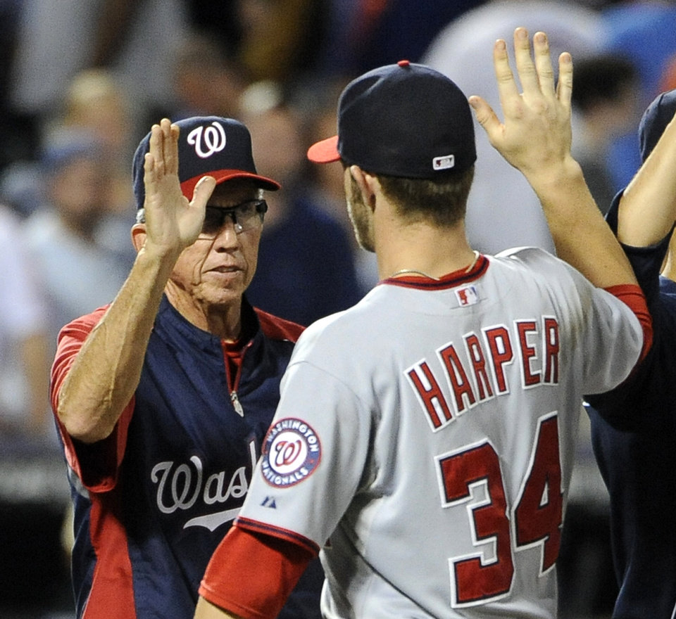 FILE - In this July 24, 2012 file photo, Washington Nationals manager Davey Johnson high-fives Bryce Harper (34) after the Nationals defeated the New York Mets in a baseball game, at Citi Field in New York. One\'s the oldest manager in the majors. The other put together the best season by a teen hitter since the 1960s. Davey Johnson, 69, and Bryce Harper, 19, were born a half-century apart, and they came together to help the Washington Nationals build the best record in baseball in 2012.