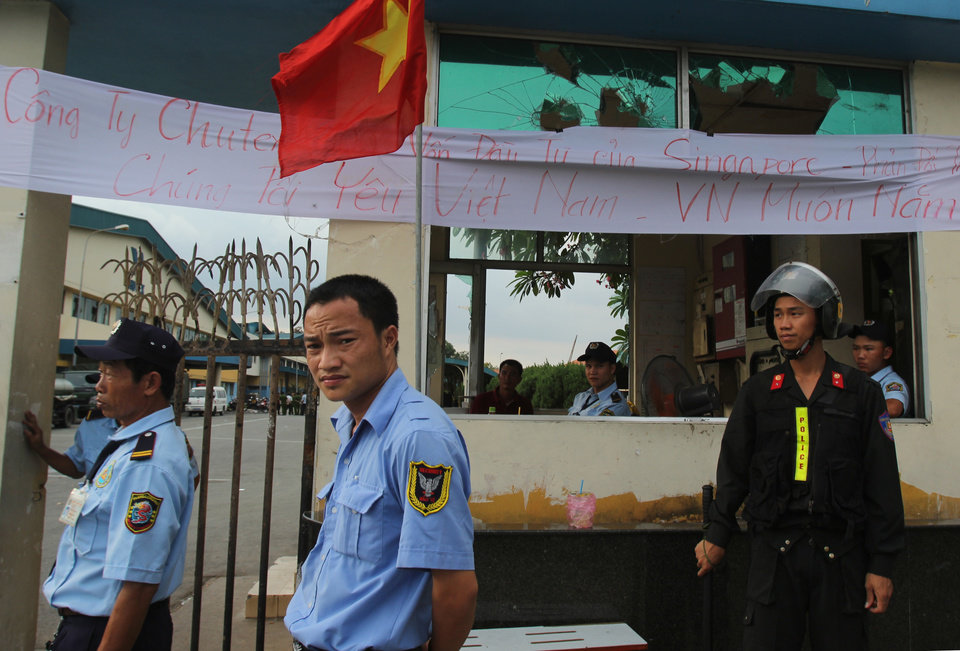 Photo - Security staff guard the entrance to a Singaporean factory in an industrial park in Binh Duong province, Vietnam Saturday, May 17, 2014, after mobs attacked foreign owned factories following anti-China protests. Vietnam's prime minister ordered an end Saturday to all