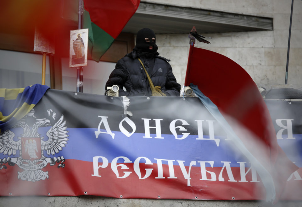 Photo - A masked pro-Russian activist looks from a balcony of the regional administration building decorated with a banner reading