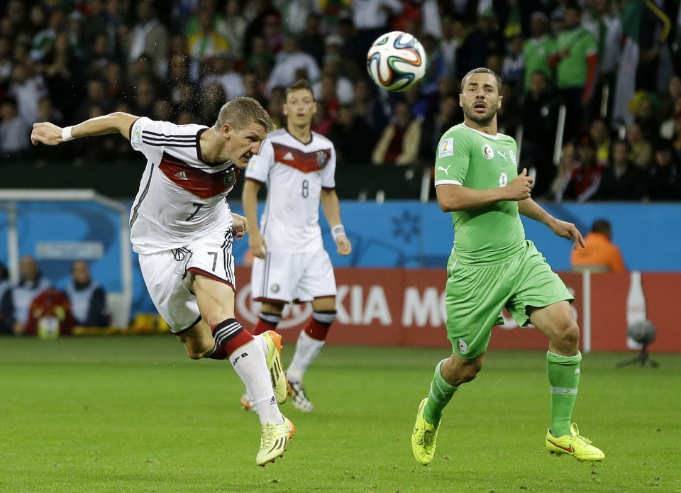 Photo - Germany's Bastian Schweinsteiger, left, heads the ball at the Algerian goal during the World Cup round of 16 soccer match between Germany and Algeria at the Estadio Beira-Rio in Porto Alegre, Brazil, Monday, June 30, 2014. (AP Photo/Kirsty Wigglesworth)