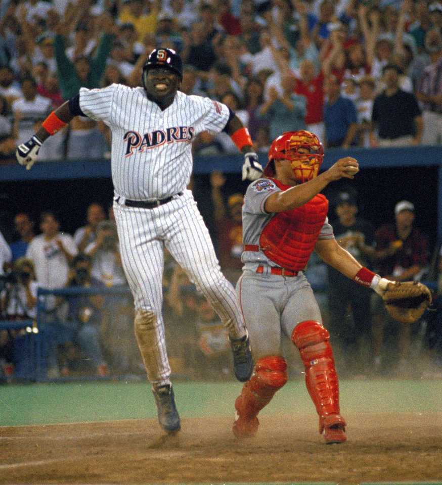 Photo - FILE - In this July 12, 1994 file photo, San Diego Padres' Tony Gwynn leaps in the air after sliding home safely to score the winning run as Texas Rangers catcher Ivan Rodriguez stands by in the 10th inning of the MLB All-Star Game at Pittsburgh's Three Rivers Stadium. The Baseball Hall of Fame said Gwynn died of cancer on Monday, June 16, 2014. He was 54. (AP Photo/Carlos Osorio, File)