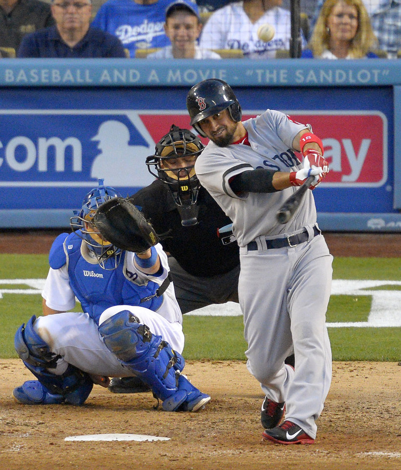 Photo - Boston Red Sox's Shane Victorino, right, hits a solo home run as Los Angeles Dodgers catcher A.J. Ellis, left, and home plate umpire Brian Knight look on during the seventh inning of their baseball game, Sunday, Aug. 25, 2013, in Los Angeles.  (AP Photo/Mark J. Terrill)