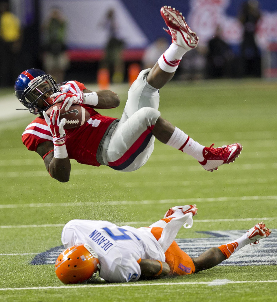 Photo - Mississippi running back Mark Dodson is upended by Boise State cornerback Donte Deayon during an NCAA college football game Thursday, Aug. 28, 2014, in Atlanta. Mississippi won 35-13. (AP Photo/The Idaho Statesman, Darin Oswald)