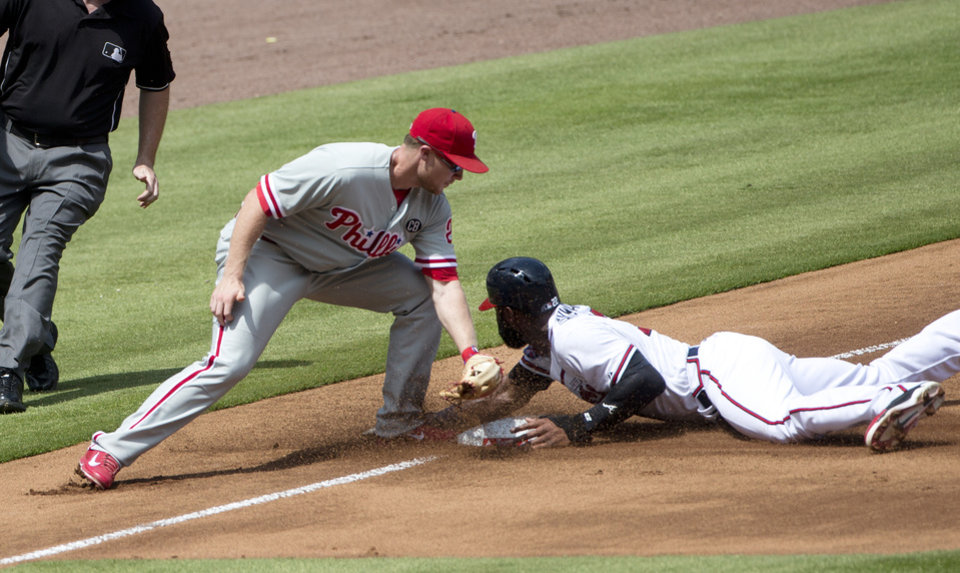 Photo - Atlanta Braves right fielder Jason Heyward (22) steals third base as Philadelphia Phillies third baseman Cody Asche (25) applies the late tag in the first inning of a baseball game Monday, Sept. 1, 2014, in Atlanta. (AP Photo/John Bazemore)