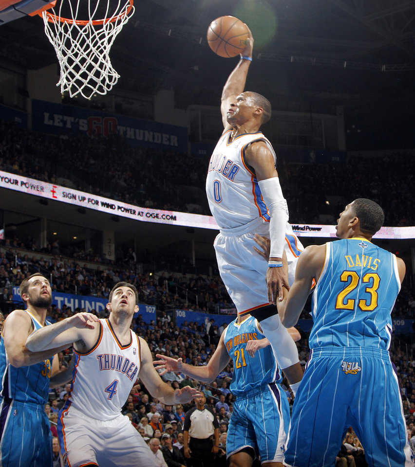 Photo - Oklahoma City Thunder's Russell Westbrook (0) dunks the ball over New Orleans Hornets' Anthony Davis (23) during the NBA basketball game between the Oklahoma CIty Thunder and the New Orleans Hornets at the Chesapeake Energy Arena on Wednesday, Dec. 12, 2012, in Oklahoma City, Okla.   Photo by Chris Landsberger, The Oklahoman