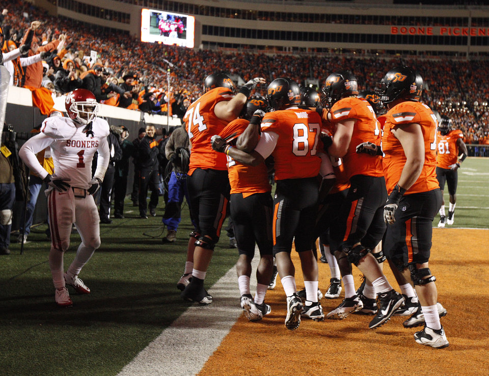 Photo - CELEBRATION: Oklahoma's Tony Jefferson (1) watches as Oklahoma State celebrates a Jeremy Smith touchdown during the Bedlam college football game between the Oklahoma State University Cowboys (OSU) and the University of Oklahoma Sooners (OU) at Boone Pickens Stadium in Stillwater, Okla., Saturday, Dec. 3, 2011. Photo by Bryan Terry, The Oklahoman