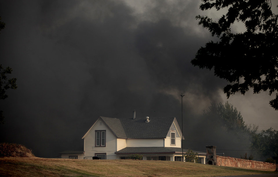 Photo - A smoke surrounds a home as a wildfire burns in Luther, Okla., Friday, Aug. 3, 2012. Photo by Sarah Phipps, The Oklahoman