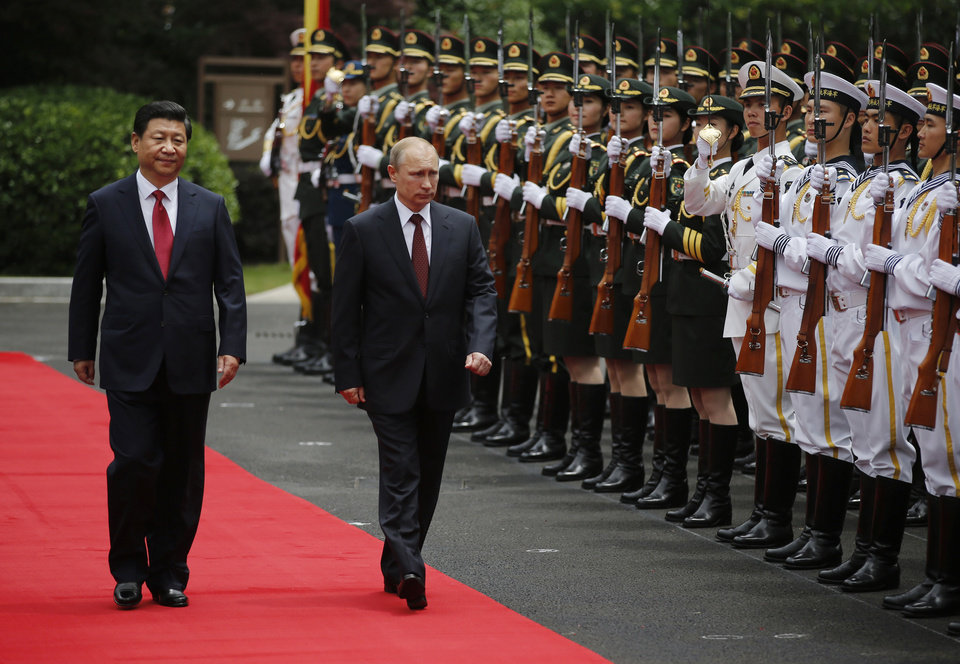 Photo - Russia's President Vladimir Putin, center, and China's President Xi Jinping, left, review an honor guard during a welcoming ceremony at the Xijiao State Guesthouse ahead of the fourth Conference on Interaction and Confidence Building Measures in Asia (CICA) summit, in Shanghai, China Tuesday, May 20, 2014. (AP Photo/Carlos Barria, Pool)