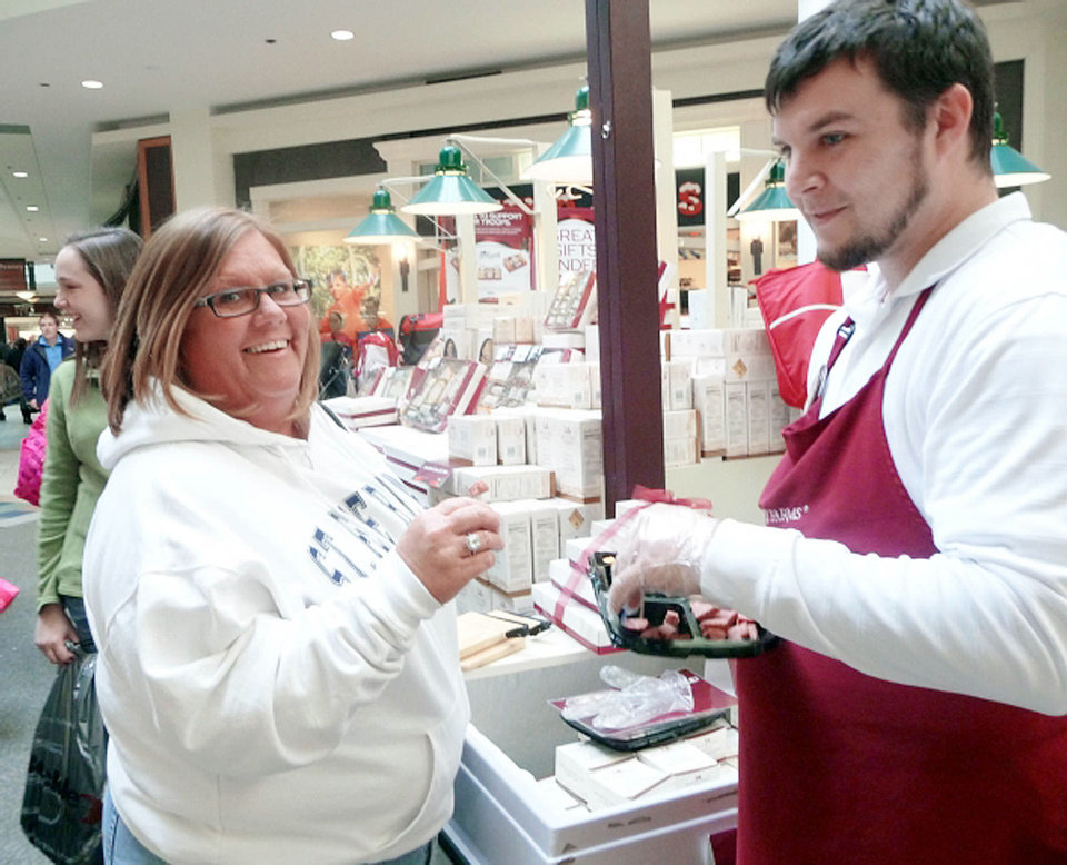 Ryan Heater, Quail Springs Mall�s Hickory Farms store team leader, hands out a sample to Loretta Sapp during Black Friday shopping.