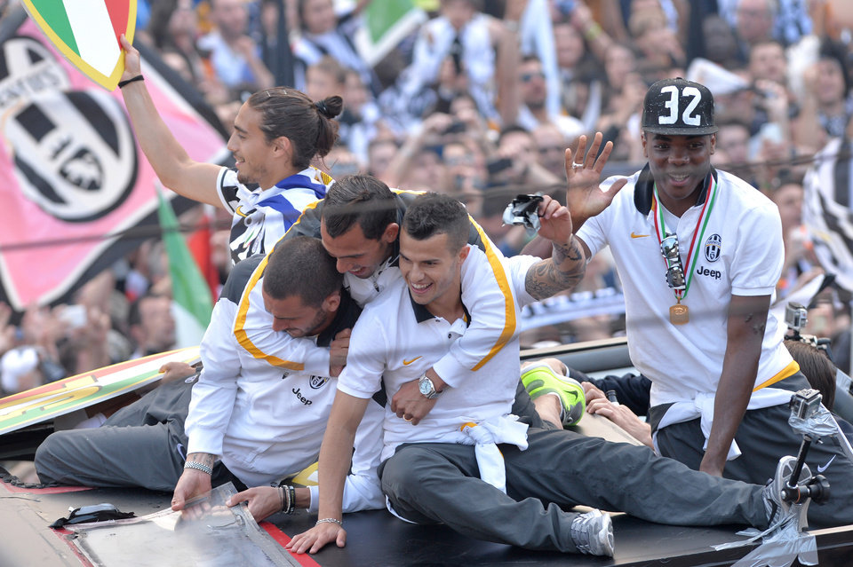 Photo - Juventus' players stand on a bus parading in downtown Turin, Italy, as they celebrate at the end of a Serie A soccer match between Juventus and Cagliari, Sunday, May 18, 2014. Juventus celebrated its third straight Serie A title with a 3-0 home victory over Cagliari to set a new European record of 102 points. Antonio Conte's side had already broken the Serie A points record but ensured it moved into triple figures by also becoming the first Italian side to maintain a 100% home record. (AP Photo/Massimo Pinca)