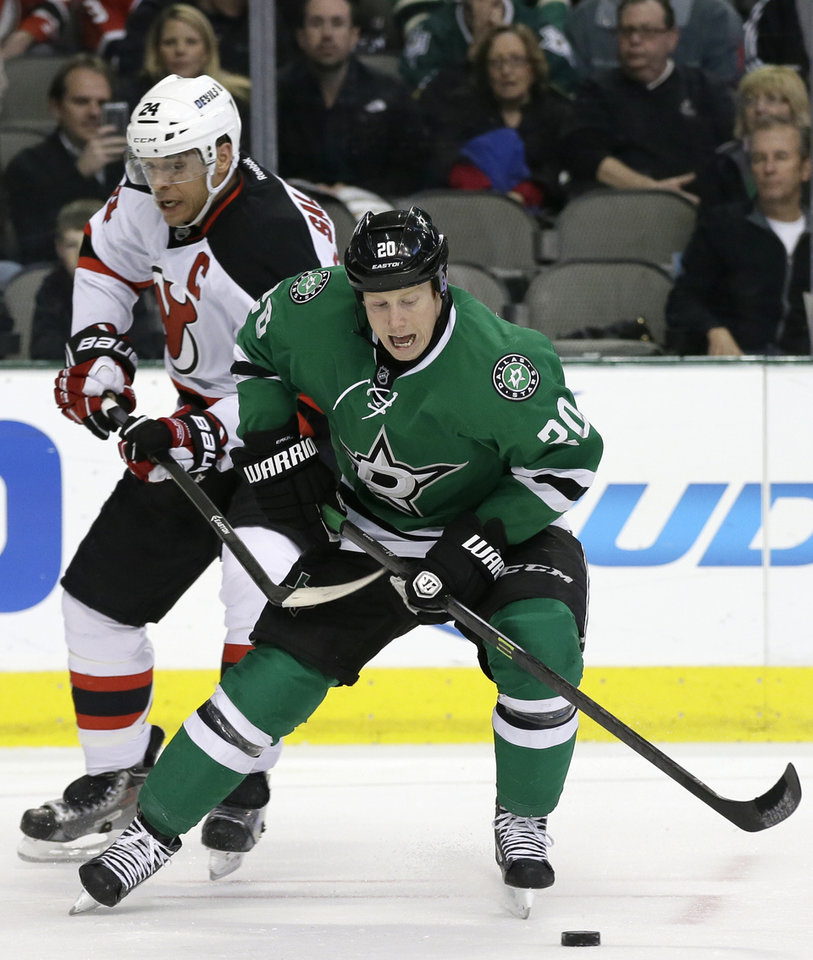 Photo - Dallas Stars' Cody Eakin (20) fights for control of the puck against pressure from New Jersey Devils' Bryce Salvador (24) in the first period of an NHL hockey game on Thursday, Jan. 30, 2014, in Dallas. (AP Photo/Tony Gutierrez)