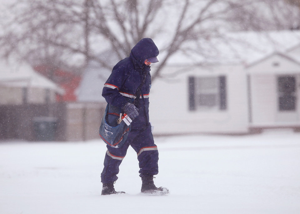 Photo - Mail carrier David Alexander lowers his head and walks through snow delivering mail in a Midwest city neighborhood near SE 15 and Lockheed.  Alexander, who has worked for the post office for 26 years, said the most difficult part of delivering the mail in this weather is walking through the snow. He said the sub-freezing temperatures don't bother him too much because he dresses for the cold. He wears five layers of clothing above the waist and three layers of clothing below the waist. He wears thermal undershirts and pants. On his feet, he wears boots.  He wears gloves and a mask around his face. A second winter storm in a week dumped about 6 inches of snow in the Oklahoma City area Tuesday morning, Feb. 9, 2011.   Photo by Jim Beckel, The Oklahoman