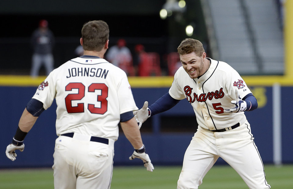 Photo - Atlanta Braves' Freddie Freeman, right, celebrates with teammate Chris Johnson after Freeman hit a single to score the game winning run in the tenth inning of a baseball game against the Cincinnati Reds, Sunday, April 27, 2014, in Atlanta. The Braves won 1-0. (AP Photo/David Goldman)