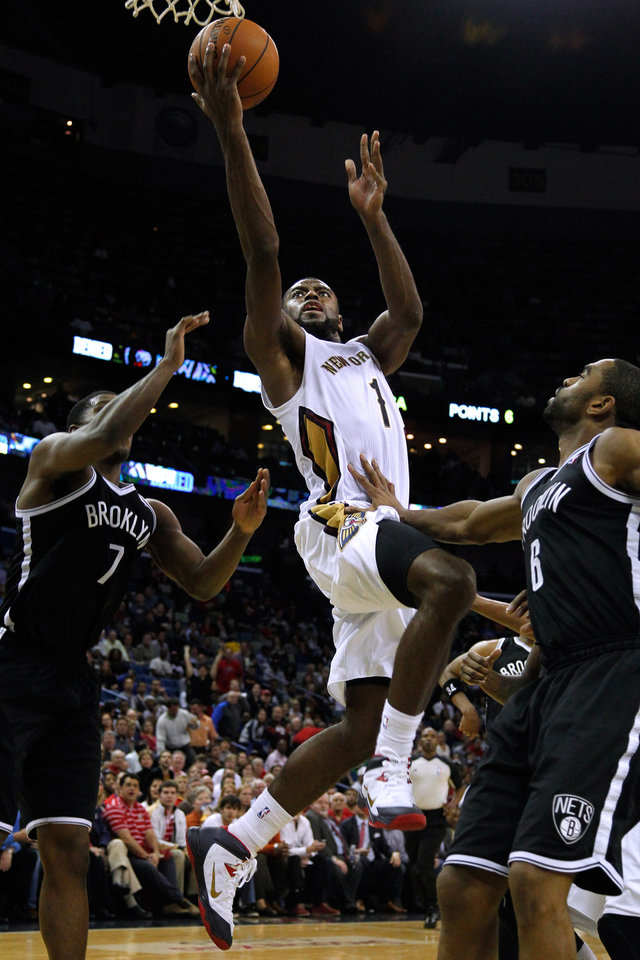 Photo - New Orleans Pelicans forward Tyreke Evans (1) drives to the basket against Brooklyn Nets guard Joe Johnson (7) and Brooklyn Nets forward Alan Anderson (6) during the second half of an NBA basketball game in New Orleans, Monday, March 24, 2014. The Pelicans won 109-104. (AP Photo/Jonathan Bachman)