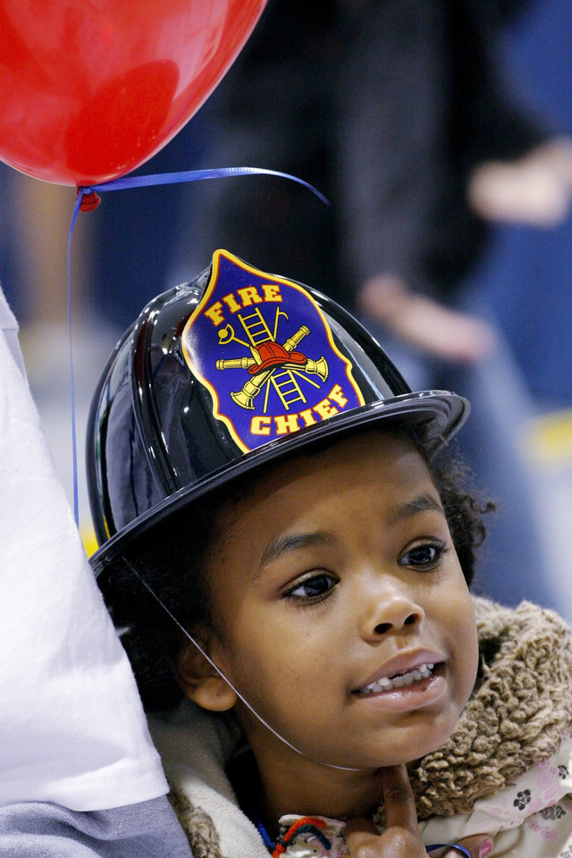Photo - Trinity Pendleton, 6, sports a fire chief hat and a balloon she received at the Moore Fun Safety Fair in the Moore Community Center Saturday, May 2, 2009. Photo by Doug Hoke, The Oklahoman
