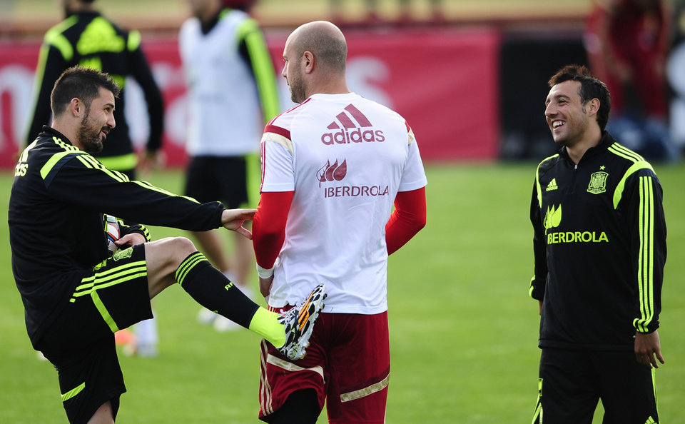 Photo - Spain's David Villa, left, jokes with goalkeeper Pepe Reina, center, and Santi Cazorla, right, during a training session at the Atletico Paranaense training center in Curitiba, Brazil, Monday, June 9, 2014. Spain will play in group B of the Brazil 2014 World Cup. (AP Photo/Manu Fernandez)