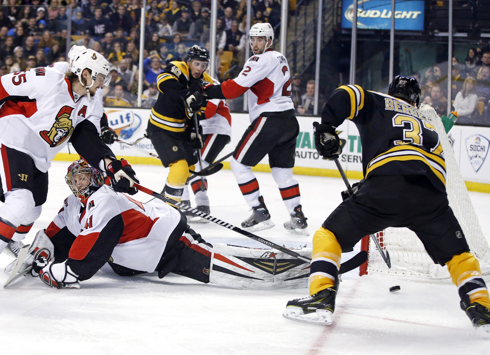 Photo - Boston Bruins center Patrice Bergeron (37) maneuvers the puck for a goal as Ottawa Senators goalie Craig Anderson (41) lies on the ice with Senators defenseman Erik Karlsson (65) trying to defend during the second period of an NHL hockey game in Boston, Saturday, Feb. 8, 2014. Senators defenseman Jared Cowen (2) covers Bruins right wing Reilly Smith (18). (AP Photo/Elise Amendola)
