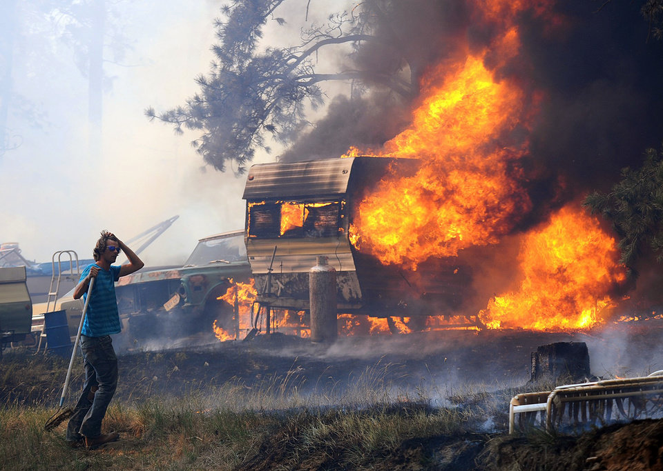 Photo -   Volunteers and firefighters from the Dean Creek Fire Department work to save a home south of Roundup, Mont. on June 26, 2012. Hundreds of families were forced from their homes south of Roundup as a fire pushed by strong winds burned more than 18,000 acres. (AP Photo/The Billings Gazette, Larry Mayer)
