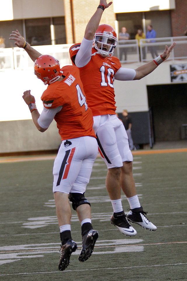 Photo - Oklahoma State's J.W. Walsh (4) and Clint Chelf (10) celebrate a touchdown during the college football game between the Oklahoma State University Cowboys (OSU) and Texas Tech University Red Raiders (TTU) at Boone Pickens Stadium on Saturday, Nov. 17, 2012, in Stillwater, Okla.   Photo by Chris Landsberger, The Oklahoman