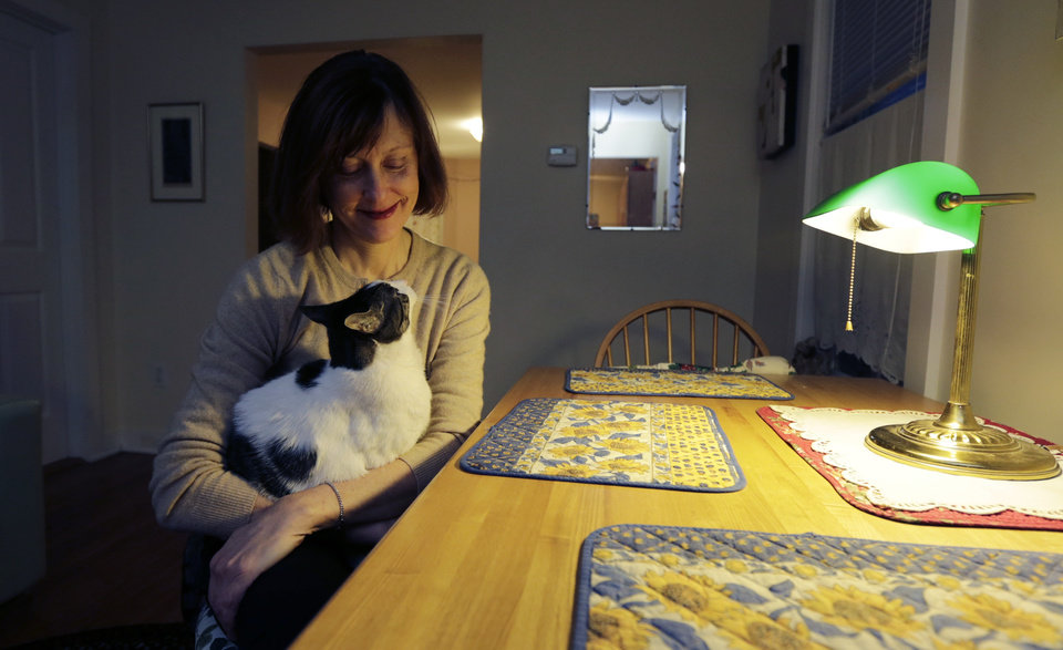 Valerie Spain poses with her pet cat at the kitchen table of her Cambridge, Mass., home, Thursday, Jan. 17, 2013. The 57-year-old former operations manager was able to find insurance through the subsidized Commonwealth Care program created under the a Massachusetts healthcare law. She pays no premiums, but is charged a $20 co-pay for visits to her doctor\'s office. (AP Photo/Charles Krupa)