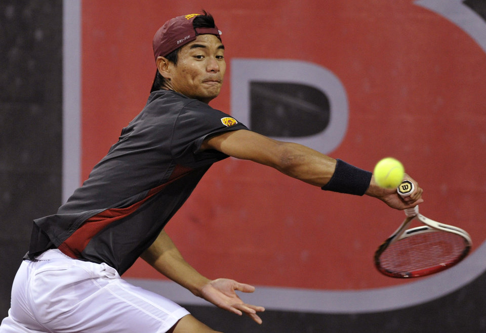 Photo - USC's Ray Sarmiento returns a volley to Oklahoma's Axel Alvarez during a men's team singles match in the NCAA Division I tennis championships, Tuesday, May 20, 2014, in Athens, Ga. USC defeated Oklahoma to take the title. (AP Photo/David Tulis)