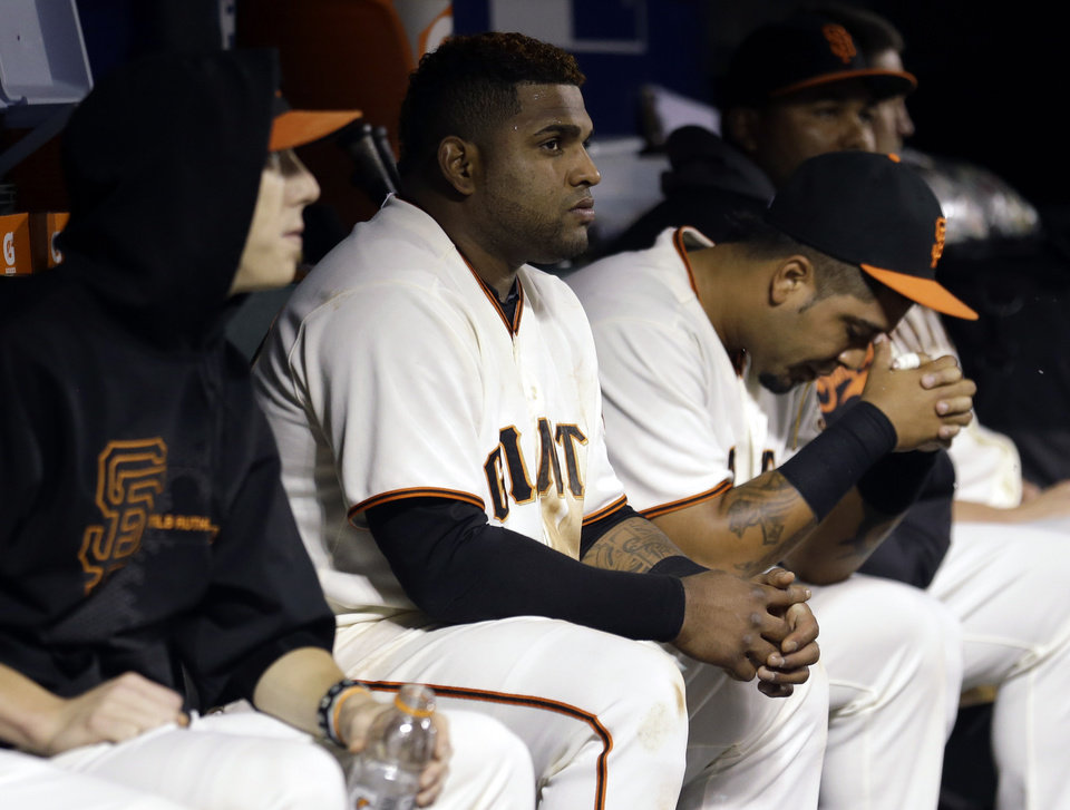 Photo -   San Francisco Giants third baseman Pablo Sandoval, center, and teammates Tim Lincecum, left, and Hector Sanchez, right, react as the team loses 9-0 during Game 2 of the National League division baseball series against the Cincinnati Reds in San Francisco, Sunday, Oct. 7, 2012. (AP Photo/Marcio Jose Sanchez)