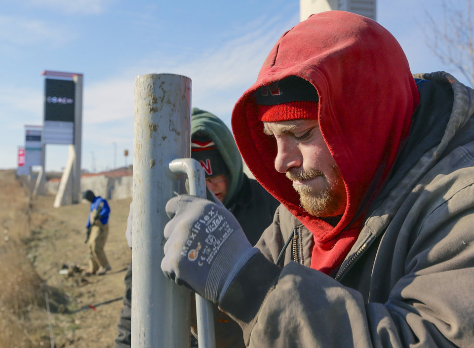 Craig Sheldon is all bundled up as he plants fence posts into the ground in sub-freezing conditions, in Gretna, Neb., Friday, Dec. 6, 2013. The temperature registered 10 degrees and the wind chill was -7 Fahrenheit as a cold snap enveloped the mid-section of the nation. (AP Photo/Nati Harnik)