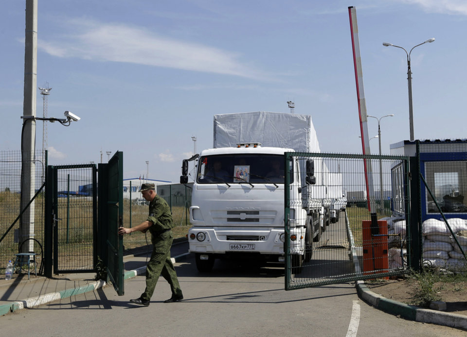 Photo - A Russian border guard opens a gate into the Ukraine for the first trucks heading into the country from the Russian town of Donetsk, Rostov-on-Don region, Russia, Friday, Aug. 22, 2014. The first trucks in a Russian aid convoy crossed into eastern Ukraine on Friday, seemingly without Kiev's approval, after more than a week's delay amid suspicions the mission was being used as a cover for an invasion by Moscow.(AP Photo/Sergei Grits)
