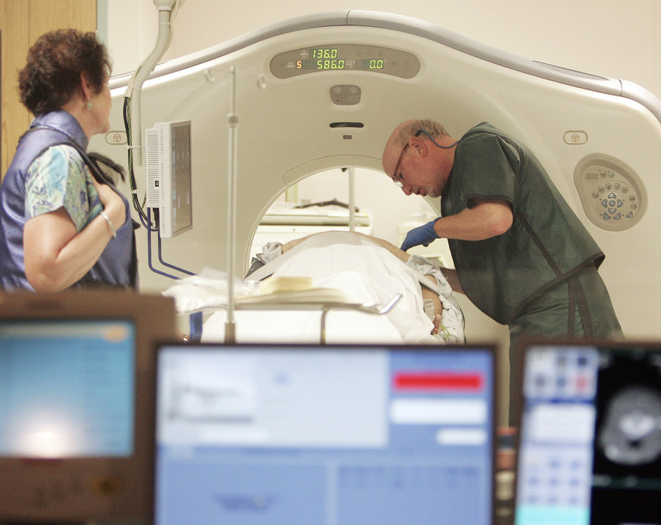 Photo - FILE - In this June 3, 2010, file photo, Dr. Steven Birnbaum works with a patient in a CT scanner at Southern New Hampshire Medical Center in Nashua, N.H. A new study estimates that screening certain current and former smokers for lung cancer would cost Medicare about $2 billion a year, which would add $3 a month to Medicare premiums. (AP Photo/Jim Cole, File)