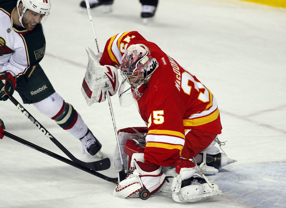 Photo - Minnesota Wild's Jason Zucker, left, tries to get the puck past Calgary Flames goalie Joey MacDonald during the second period of an NHL hockey game in Calgary, Alberta, Saturday, Feb. 23, 2013. (AP Photo/The Canadian Press, Jeff McIntosh)