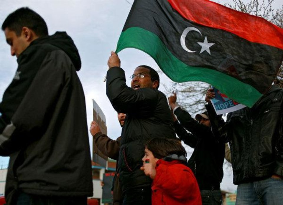 Photo - Salah Abdalhfed joins other Libyan immigrants and students protesting Moammar Gadhafi and the current situation in Libya NW 23 and Classen Avenue on Monday evening.  John Clanton - The Oklahoman