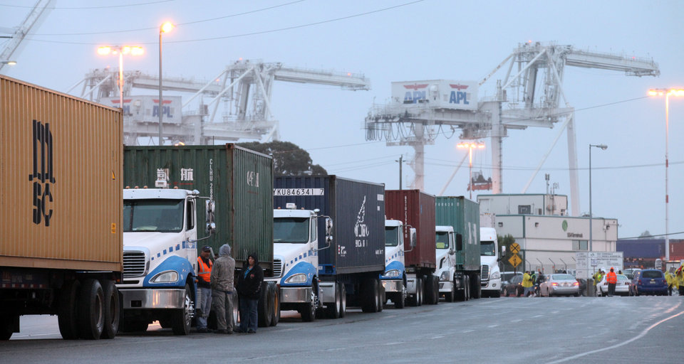 Photo -   Trucks line up along Middle Harbor Road not able to enter the port to drop off their loads due to a 24-hour strike by port workers represented by the SEIU Local 1021 at the Port of Oakland in Oakland, Calif., in the early morning hours on Tuesday, Nov. 20, 2012 (AP Photo/The Tribune,Laura A. Oda )