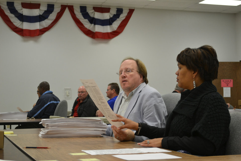 Photo - Employees of the Oklahoma County Election Board county ballots manually Wednesday during a recount of the Nov. 6 county sheriff election  The Oklahoman - Zeke Campfield
