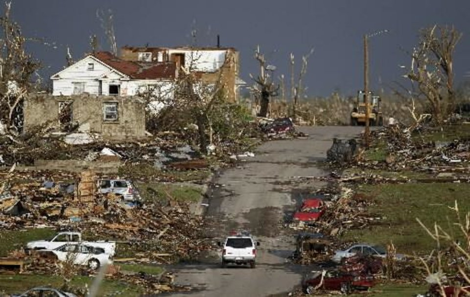 Photo - An emergency vehicle drives through a severely damaged neighborhood in Joplin, Mo., Monday, May 23, 2011. A large tornado moved through much of the city Sunday, damaging a hospital and hundreds of homes and businesses and killing at least 89 people. (AP Photo/Charlie Riedel)
