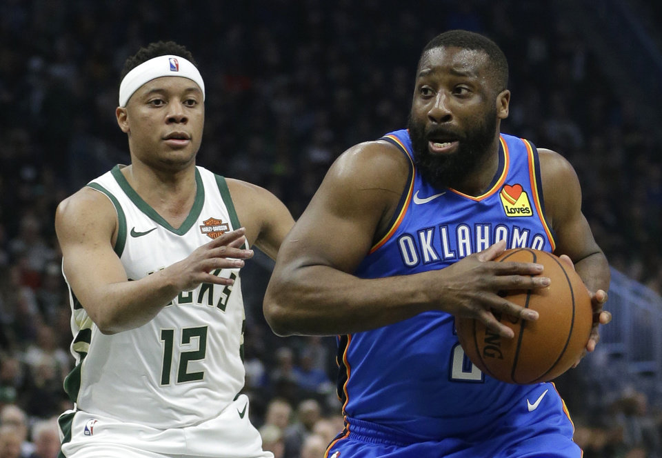 Photo - Oklahoma City Thunder's Raymond Felton, right, drives to the basket against Milwaukee Bucks' Tim Frazier during the first half of an NBA basketball game Wednesday, April 10, 2019, in Milwaukee. (AP Photo/Aaron Gash)