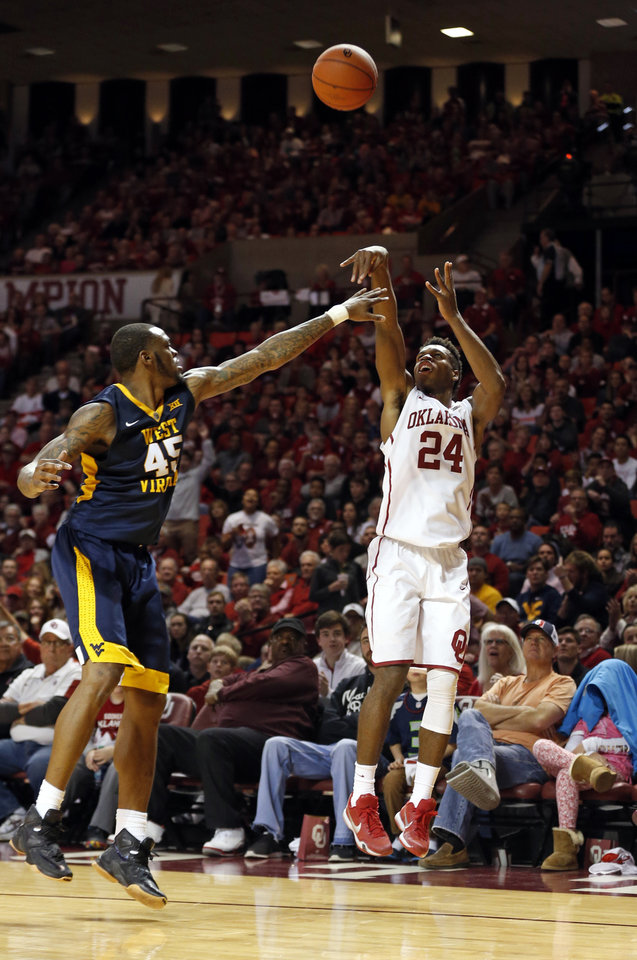 Photo - Oklahoma's Buddy Hield (24) shoots a three point shot in front of West Virginia's Elijah Macon (45) as the University of Oklahoma Sooner (OU) men play the West Virginia Mountaineers (WV) in NCAA, college basketball at The Lloyd Noble Center on Jan. 16, 2016 in Norman, Okla. Photo by Steve Sisney, The Oklahoman