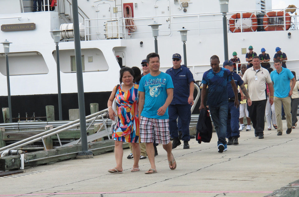 Photo - Passengers return to land at the Coast Guard station on Tybee Island, Ga., on Wednesday, July 16, 2014, after being stranded overnight on a casino boat that ran aground off the Georgia coast. More than 120 passengers and crew were aboard the Escapade casino boat when got stuck on rocks late Tuesday. The Coast Guard took them off the ship and onto rescue boats Wednesday afternoon. (AP Photo/Russ Bynum)