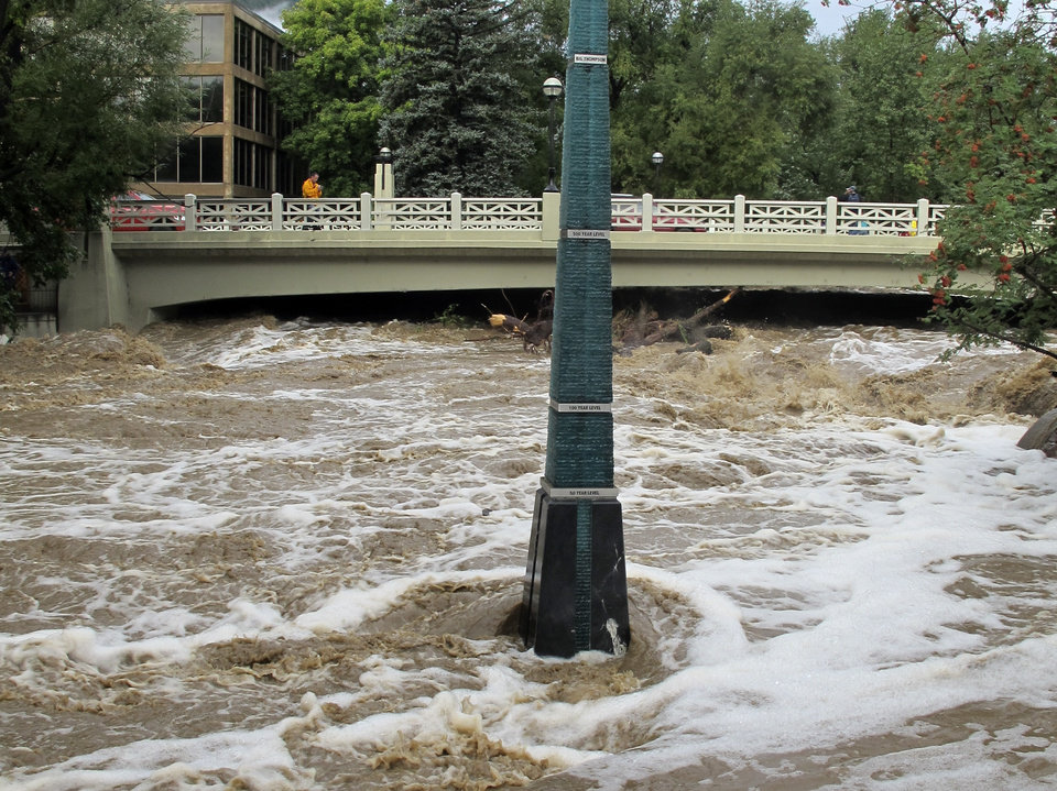 Photo - Rain-swollen Boulder Creek flows around a marker that shows historic flood levels on Friday morning, Sept. 13, 2013, in Boulder, Colo. City officials ordered an evacuation of thousands of residents along the creek the night before. Coffee-colored floodwaters cascaded downstream from the Colorado Rockies on Friday, spilling normally scenic mountain rivers and creeks over their banks and forcing thousands more evacuations(AP Photo/Ben Neary)