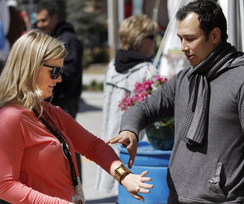 Photo - Artist Daniel Schemel talks about his watches with Stacy Hawthorne as she tries one on at the Festival of the Arts in downtown Oklahoma City  Wednesday, April 24, 2013. The Hunters are from Piedmont. Photo by Doug Hoke, The Oklahoman