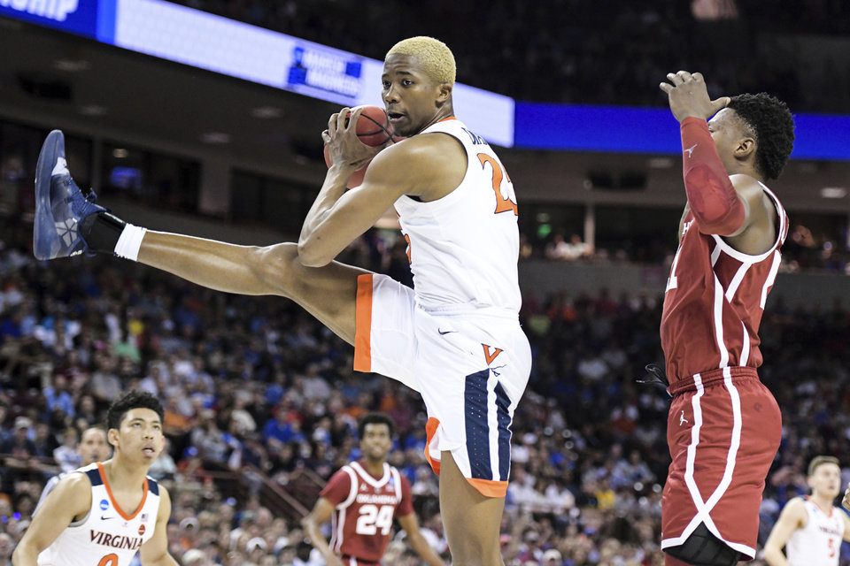 Photo - Virginia forward Mamadi Diakite (25) grabs a rebound against Oklahoma forward Kristian Doolittle, right, during the first half of a second-round game in the NCAA men's college basketball tournament Sunday, March 24, 2019, in Columbia, S.C. (AP Photo/Sean Rayford)