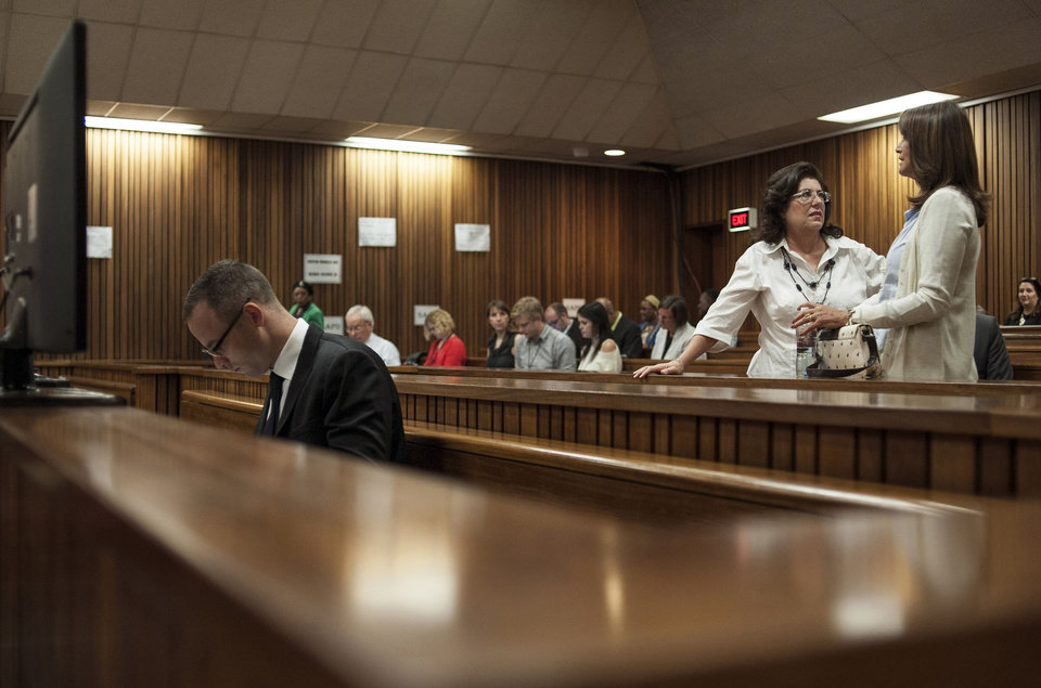 Photo - Oscar Pistorius, left, sits in a courtroom at the high court in Pretoria, South Africa, Monday May 5, 2014 at the resumption of his murder trial, following a two-week break. Pistorius' murder trial enters a critical phase Monday as his defense team attempts to recover from a faltering start and reinforce the disabled athlete's claim that he fatally shot girlfriend Reeva Steenkamp by mistake because he was overwhelmed by a long-held fear of violent crime. (AP Photo/Ihsaan Haffejee, Pool)