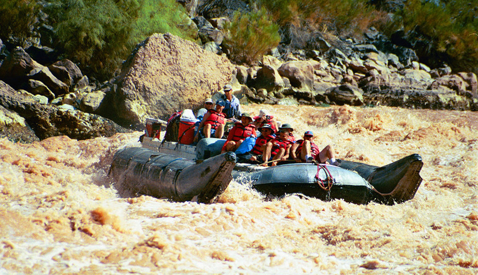 Photo -   FILE - This Aug. 31, 2002 file photo shows a group of visitors riding a pontoon raft through rapids in Grand Canyon National Park, Ariz. Thousands of people who had been on a waiting list for a coveted trip on the Colorado River through the Grand Canyon still are waiting. (AP Photo/Brian Witte, File)