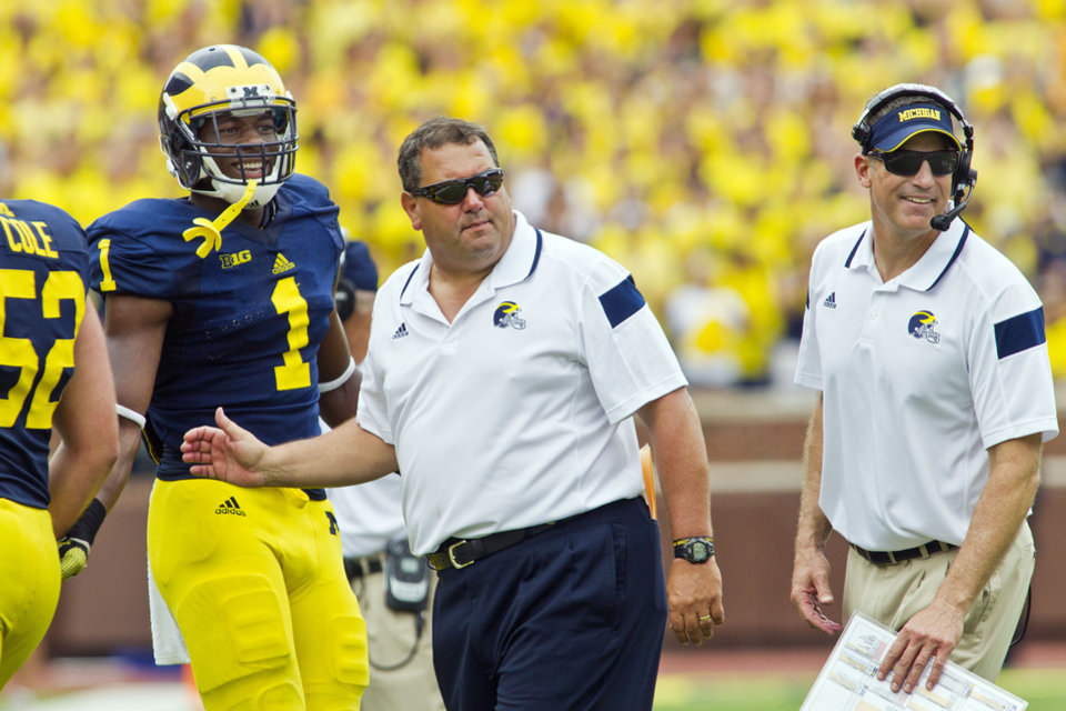 Photo - Michigan wide receiver Devin Funchess (1) stands with head coach Brady Hoke, center, and offensive coordinator Doug Nussmeier, right, greeting players coming off the field after a touchdown in the third quarter of an NCAA college football game against Appalachian State in Ann Arbor, Mich., Saturday, Aug. 30, 2014. Michigan won 52-14. (AP Photo/Tony Ding)