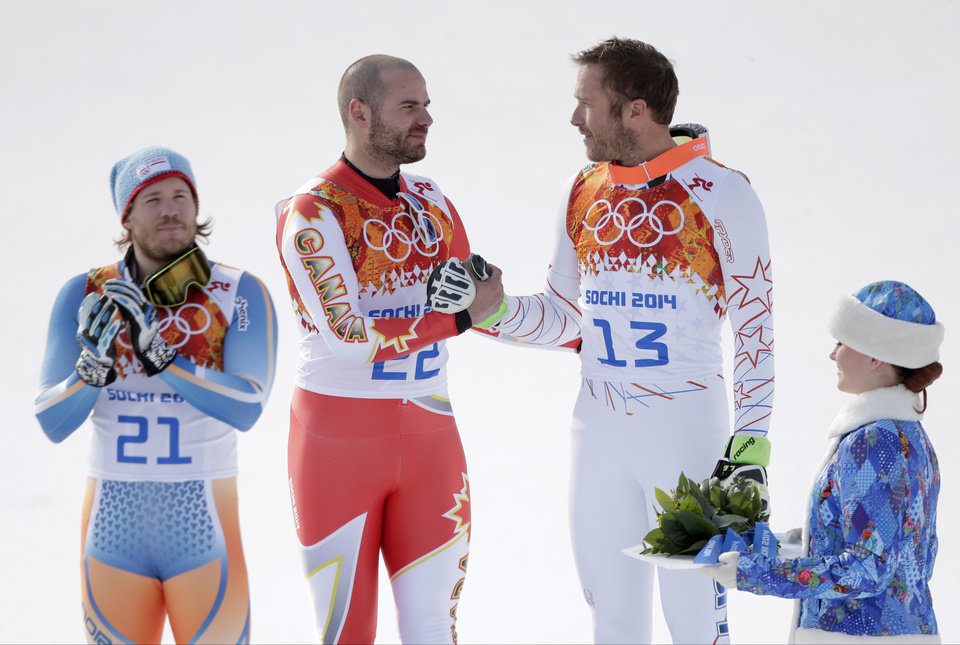 Photo - Men's super-G joint bronze medal winners Canada's Jan Hudec and United States' Bode Miller shake hands on the podium as gold medal winner Norway's Kjetil Jansrud stands at left during a flower ceremony at the Sochi 2014 Winter Olympics, Sunday, Feb. 16, 2014, in Krasnaya Polyana, Russia.(AP Photo/Charlie Riedel)